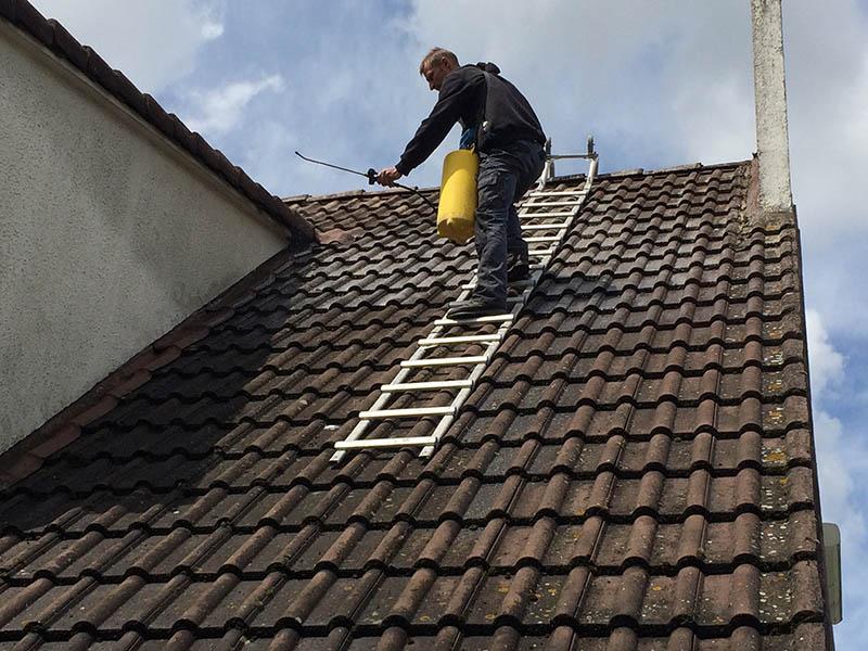 photo d'un ouvrier de kokisol pendant le nettoyage d'un toit