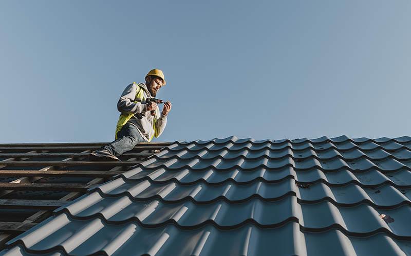 ouvrier sur un toit de tuiles foncées